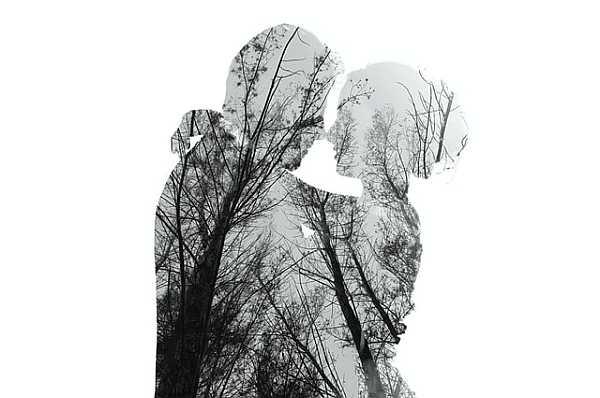 Double exposure with couple and forest