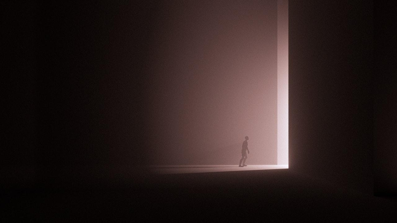 Surreal downsized man at the bottom of an open door